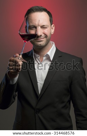 suave man in jacket tasting red wine in front of red background