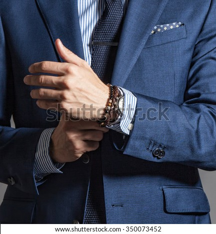 Suave modern man in casual style with bracelets on hand