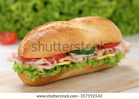 Sub deli sandwich baguette with ham, cheese, tomatoes and lettuce - stock photo