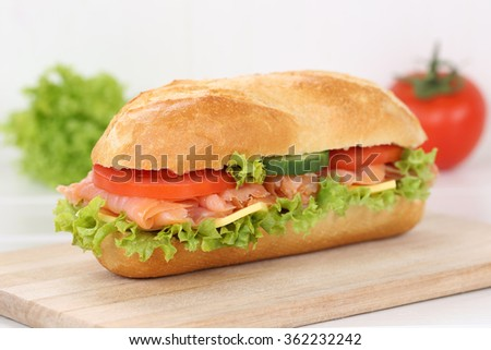 Sub deli sandwich baguette with salmon fish, cheese, tomatoes and lettuce for breakfast - stock photo