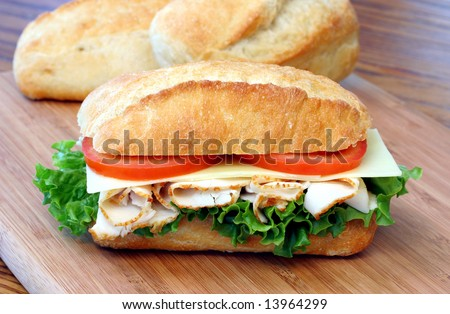 Sub sandwich of turkey, tomatoes, lettuce and cheese on a cutting board with loaves of bread behind. - stock photo
