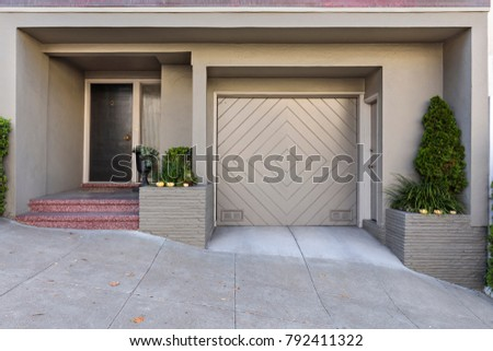 subdued green house with a one car garage door and a front entrance