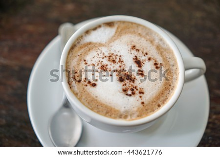 Subject is blurry and soft focus and out of focus mocha coffee on wood table