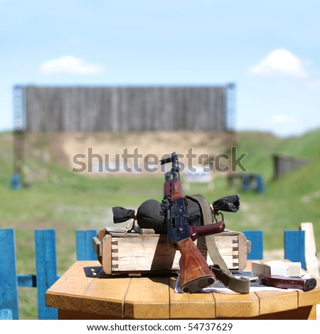 Submachine gun on shooting range. Soft focus - stock photo