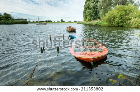 Submerged orange rowing boat near the banks of river. - stock photo
