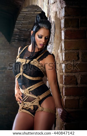 Submissive sexy woman in the old room with brick walls