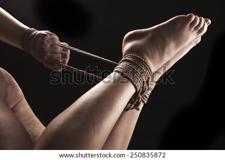 Submissive woman in hog tie bondage position on black background / BDSM theme