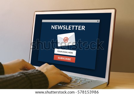 Subscribe newsletter concept on laptop computer screen on wooden table. Hands typing on a keyboard. All screen content is designed by me.