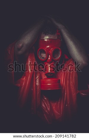 Substance, A man in a gas mask over  the smoke. black background and red colors - stock photo