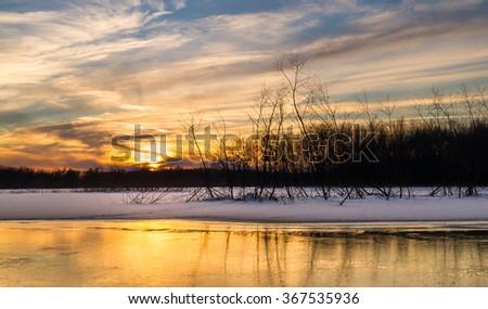 Subtle Midwest Winter sunset over the frozen Lake Huse in LaSalle, Illinois. - stock photo