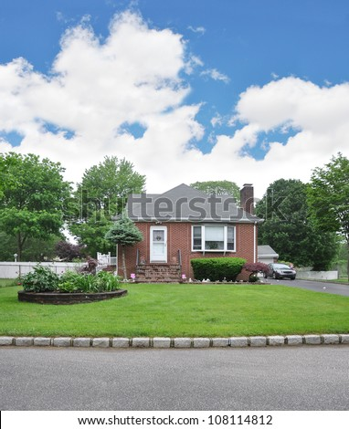 Suburban Brick Bungalow Home Landscaped Front Yard Curb Street Cloudy Blue Sky Day