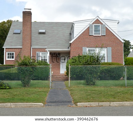 Suburban Brick Bungalow Style Home with Chain Link Fence Blacktop Walkway Blue Sky Clouds Day Residential Neighborhood USA