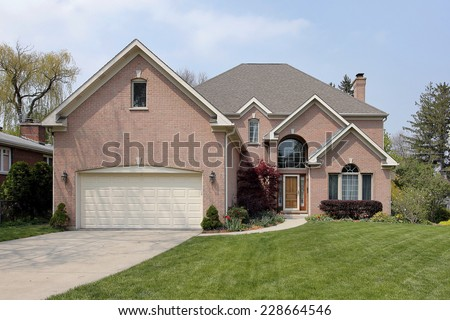 Suburban brick home with arched window above entry - stock photo