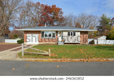 Suburban brick ranch style coral fence cement driveway home autumn blue sky day residential neighborhood USA - stock photo