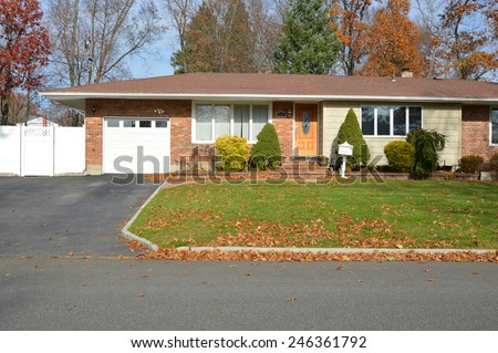 Suburban brick ranch style home white picket fence blacktop driveway autumn blue sky day residential neighborhood USA - stock photo