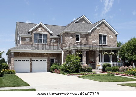 Suburban brown brick home with front porch - stock photo