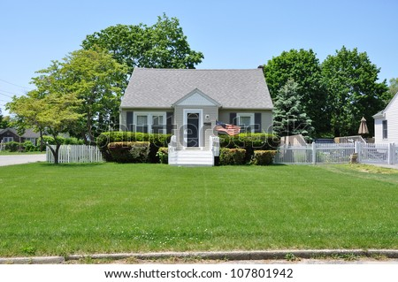 Suburban Bungalow Home American Flag Waving Residential Neighborhood Blue Sky Day - stock photo