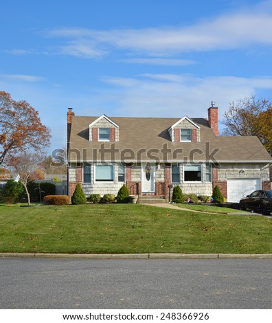 Suburban Cape Cod home landscaped beautiful autumn day residential neighborhood USA - stock photo