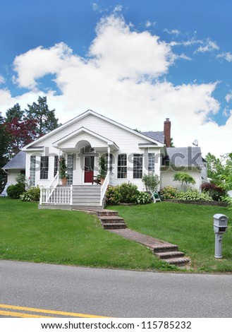 Suburban Cottage Home with Brick Steps Mailbox on curb of residential neighborhood street - stock photo