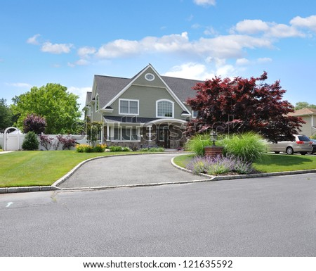 Suburban Cottage Style Home with Lavender at Driveway Curbside - stock photo