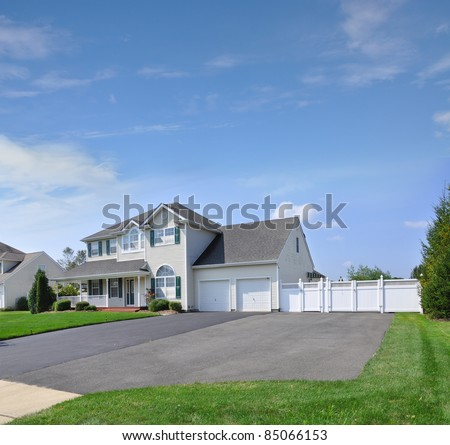 Suburban Extra Wide Blacktop Driveway of Luxury Two Story Double Garage Door White Home - stock photo