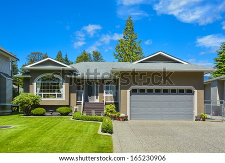 Suburban family house with concrete driveway, wide garage door on blue sky background. - stock photo
