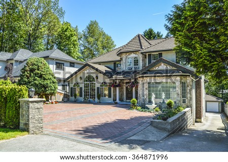 Suburban family house with paved front yard, asphalt driveway, and garage on back yard. Luxury residential house with arch windows, trees around and blue sky background. - stock photo