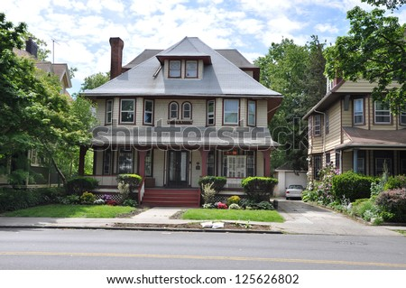 Suburban Gable Front Style Home Residential Neighborhood Sunny Blue Sky Clouds Street - stock photo
