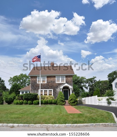 Suburban Gable Style Home with American Flag Pole Landscaped Front yard Lawn Sunny Blue Sky Clouds USA Residential Neighborhood - stock photo