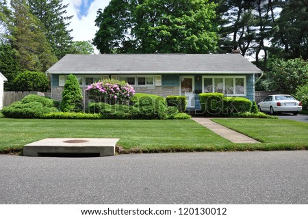 Suburban Home Ranch Style Landscaped Blooming Rhododendron and water drain at curbside of street - stock photo
