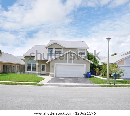 Suburban Home Snout Back Split Architecture Residential Neighborhood Blue Sky Clouds - stock photo