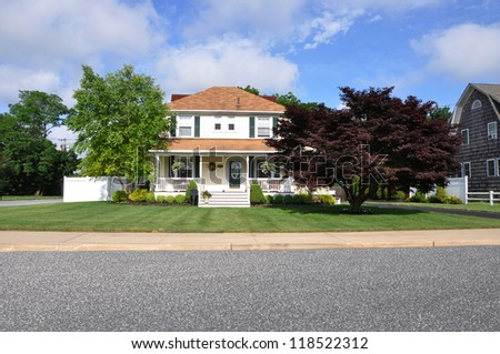 Suburban Home with Japanese Maple Tree on front yard lawn sunny blue sky day with clouds