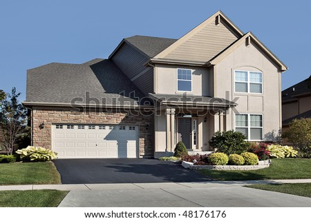 Suburban home with stone garage and covered entry - stock photo