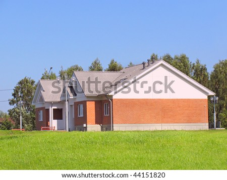 Suburban house of red brick surrounded by lawn