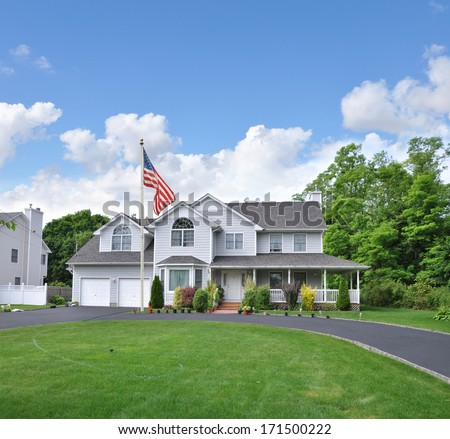 Suburban McMansion Style home Circle blacktop driveway two car garage residential neighborhood blue sky clouds USA - stock photo