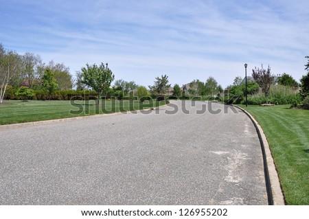 Suburban Neighborhood Street Curving Sunny Blue Sky Clouds - stock photo