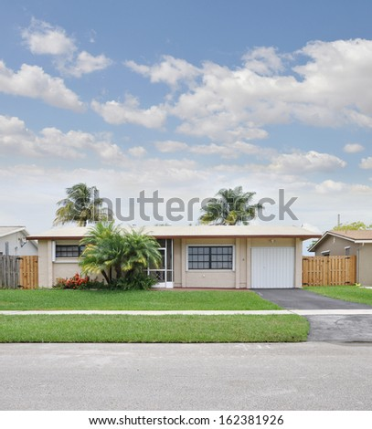 Suburban Ranch Style Home Palm Trees Landscaped House Front Blue Sky Clouds Residential Neighborhood USA - stock photo