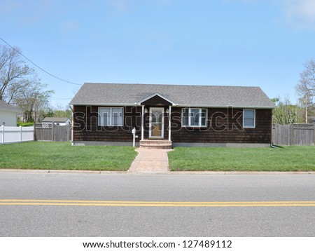 Suburban Ranch style House on Country Road with Yellow Dividing Traffic Line Sunny Blue Sky Day