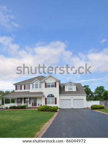 Suburban Residential Neighborhood Two Story Two Car Garage Home with Blacktop Driveway Front Yard Blue Sky - stock photo