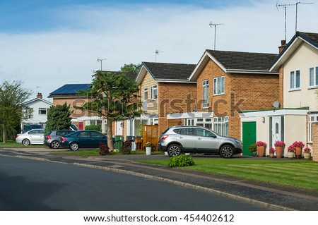 Suburban residential street with modern brick houses. - stock photo