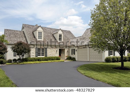 Suburban stone home with cedar shake roof - stock photo