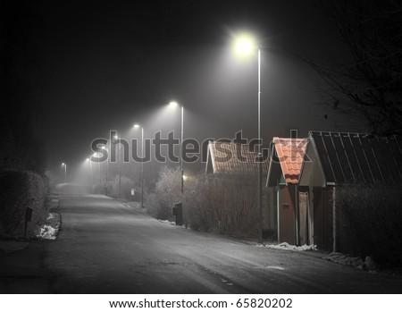 Suburban street on a foggy evening - stock photo