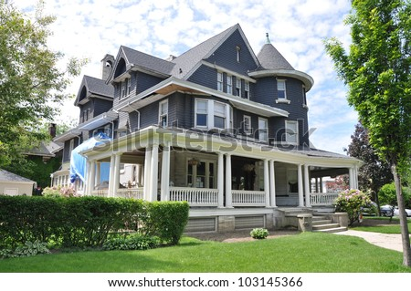 Suburban Three story tall Victorian Home under Repair Remodeling - stock photo