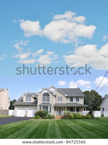 Suburban Two Car Garage Two Story Home Green Lawn Blue Cloud Sky McMansion style Architecture - stock photo