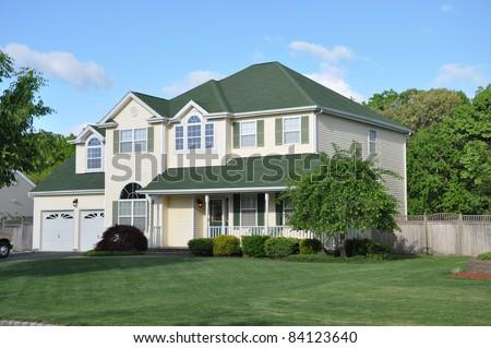 Suburban Two Story Two Car Garage Home Manicured Lawn Landscape Sunny Day - stock photo