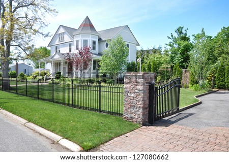 Suburban Victorian Style Home Fenced Sunny Blue Sky Day - stock photo