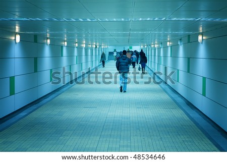 Subway blue corridor and people walking by - stock photo