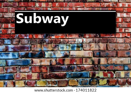 Subway or Underground sign board on a graffiti laden brick wall - stock photo