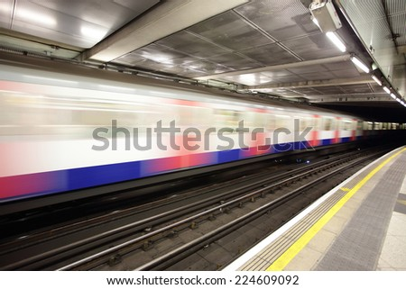 subway train in motion arriving at a London underground train station. - stock photo