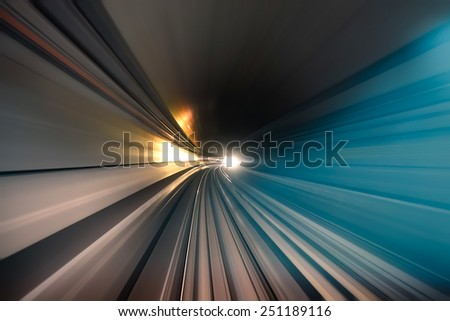 Subway tunnel with blurred light tracks in the gallery - Concept of modern metro underground transport and connection - Radial zoom motion blur due to the speed of the train - stock photo